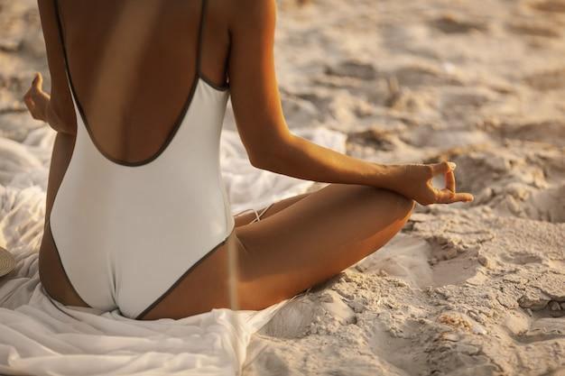 Posa di meditazione yoga con cuffie sulla spiaggia