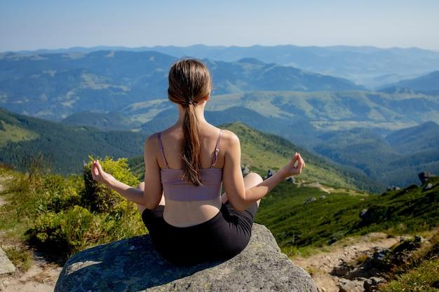 Yoga, meditazione. donna equilibrata, pratica di meditazione e yoga energetico zen in montagna. ragazza che fa sport di esercizio di forma fisica all'aperto nella mattina. concetto di stile di vita sano.