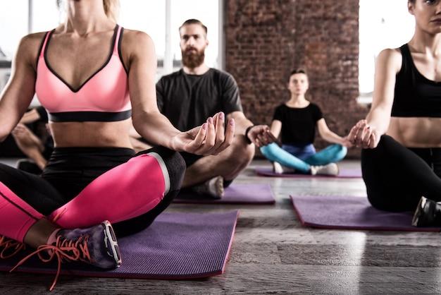 Meditazione yoga di giovani rilassati nella posa del loto nel centro fitness
