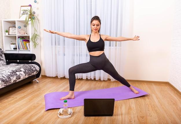 Yoga in linea sulla ragazza di stile di vita sano del computer portatile che fa yoga a casa