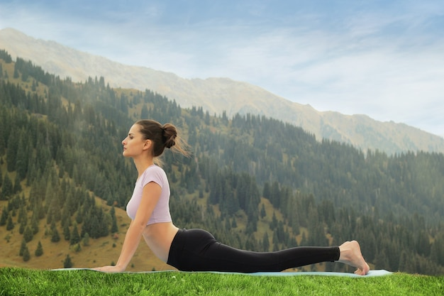 Yoga all'aperto donna che fa yoga surya namaskar saluto al sole asana urdhva mukha svanasana