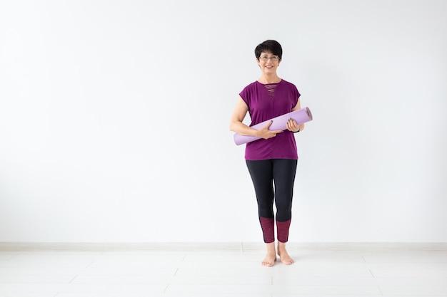 Yoga, concetto della gente - stuoia della tenuta della donna di mezza età dopo una lezione di yoga sulla superficie bianca con lo spazio della copia