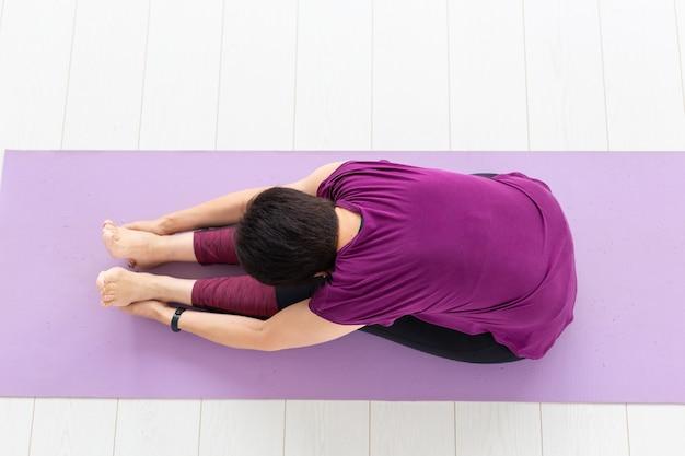Yoga, concetto di persone - una donna di mezza età che fa yoga e prova a fare un asana, vista dall'alto