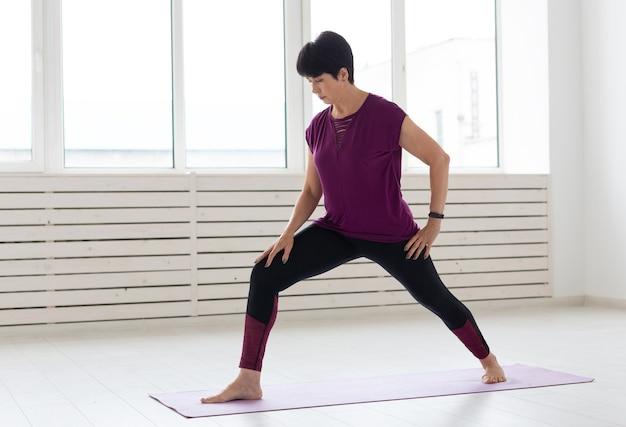 Yoga, concetto di persone - una donna di mezza età che fa yoga e prova a fare un'asana.