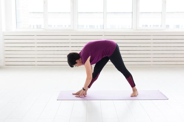 Yoga, concetto di persone - una donna di mezza età che fa yoga e prova a fare un asana.
