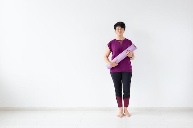 Yoga, concetto di persone - ritratto di una donna di mezza età dopo lo yoga con la sua stuoia su sfondo bianco