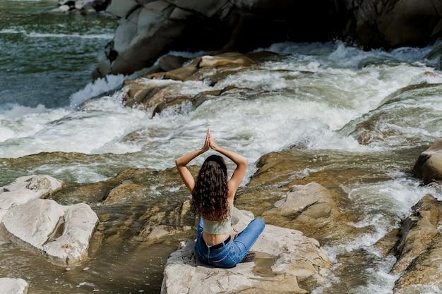 Yoga sulle rocce vicino alla cascata nel fiume di montagna. ragazza che viaggia nelle montagne di karpathian.