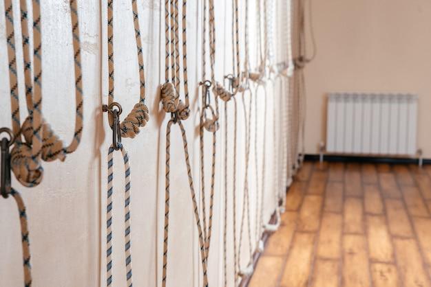 Corde di yoga che appendono sulla parete vuota dello studio. concetto di yoga iyengar