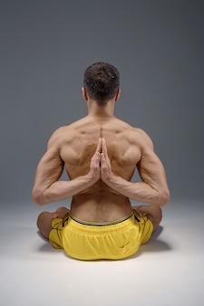 Lo yoga si siede nella posa classica con le mani dietro la schiena, posizione di meditazione, stretching perfetto, muro grigio uomo forte che fa esercizi yogi, massima concentrazione, stile di vita sano