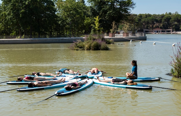 Yoga a bordo del sup. ragazze che remano a bordo di sup sul lago in città. le donne del gruppo stanno praticando (facendo) yoga, fitness, pilates e meditazione su una tavola sup. fantastico allenamento attivo all'aperto.