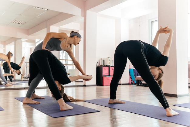 Insegnante di yoga e principiante in classe, facendo esercizi di asana. stile di vita sano nel fitness club Foto Premium