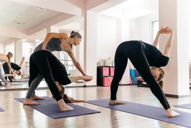 Insegnante di yoga e principiante in classe, facendo esercizi di asana. stile di vita sano nel fitness club