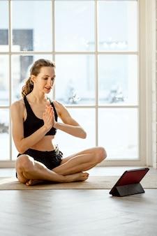 Insegnante di yoga che conduce lezione di yoga virtuale a casa in una videoconferenza.