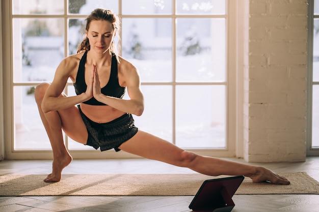 Insegnante di yoga che conduce lezione di yoga virtuale a casa in una videoconferenza