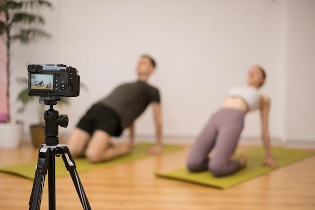 Istruttore di yoga che insegna programma di formazione online in home studio dietro la telecamera. istruttori sportivi che mostrano posizioni yoga, spiegano, danno qualche consiglio in più.