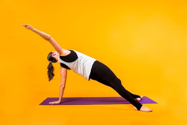 Donna di yoga che si esercita sulla stuoia