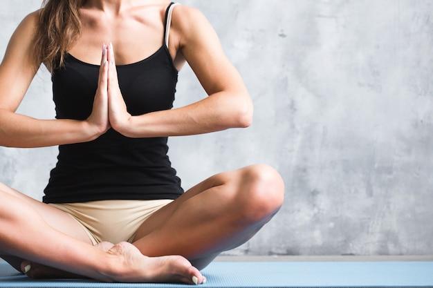 Donna di yoga nella posizione del loto in loft sportivo