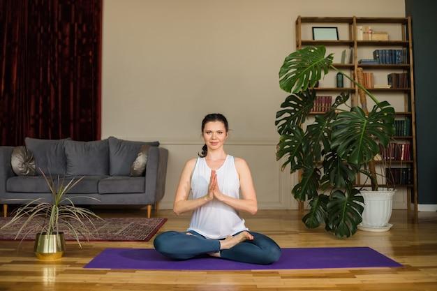 La donna di yoga si siede nella posizione del loto su un tappeto in una stanza