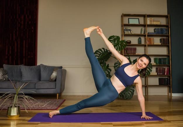 Una donna di yoga in top e leggings sta praticando un'asana su un tappeto viola nella stanza