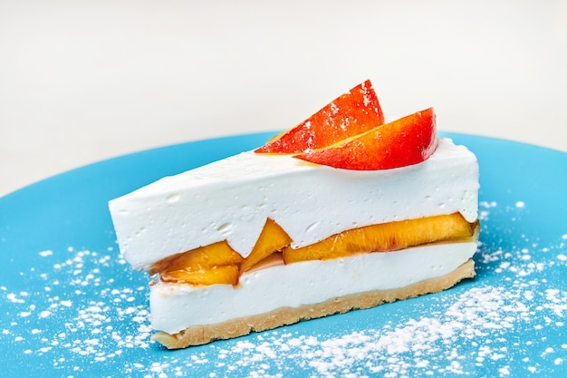 Cheesecake allo yogurt con pesche sul piatto blu