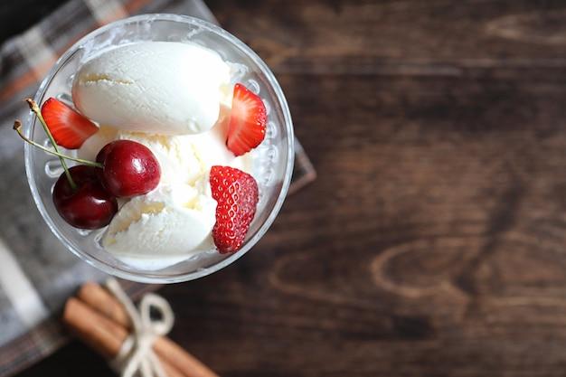 Yogurt con fragole fresche e succose e ciliegie su un tavolo di legno