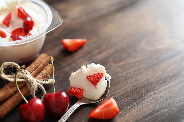 Yogurt con fragole e ciliegie fresche e succose su un tavolo di legno