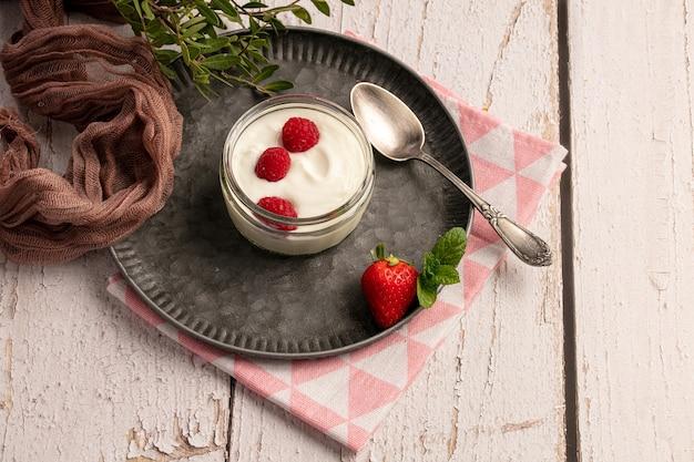 Yogurt con lamponi su una placca di metallo su un tavolo di legno bianco