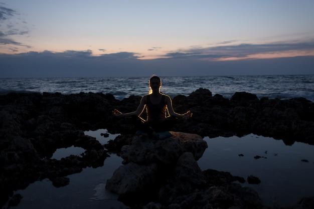 Ragazza degli yogi nella posa del loto sulle rocce vicino al mare di notte