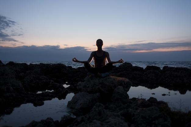 Ragazza degli yogi nella posa del loto sulle rocce vicino al mare di notte Foto Premium
