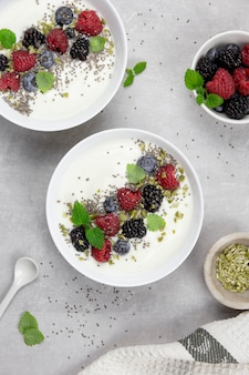 Ciotola di yogurt con frutti di bosco freschi, semi di chia, pistacchi e semi di zucca su una superficie di pietra di cemento grigio chiaro