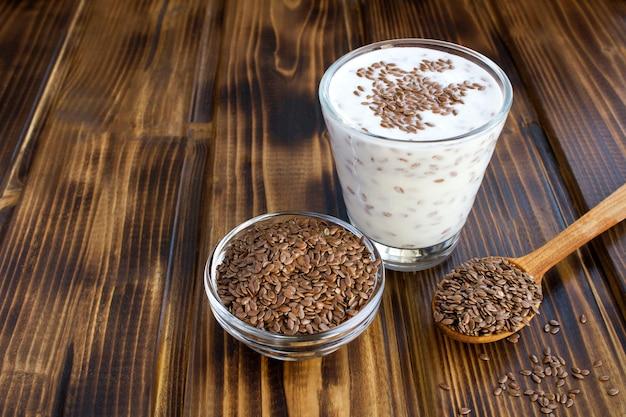 Yogurt o kefir con semi di lino nel bicchiere sulla superficie di legno marrone. copia spazio.