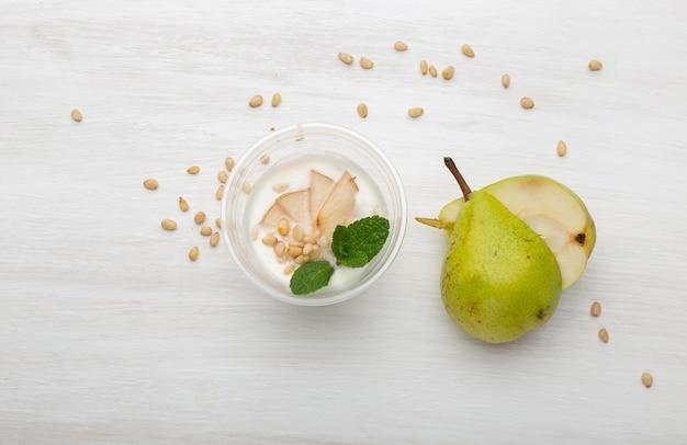 Fette di pera yogurt e menta e pinoli giacciono in una scatola da pranzo su un tavolo bianco accanto a sparsi con pinoli e fette di pera. concetto di mangiare sano.
