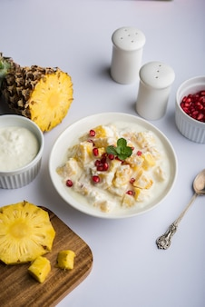 Yogurt & ananas o ananas raita, servito in una ciotola e guarnito con menta e melograno, su sfondo colorato o in legno. messa a fuoco selettiva