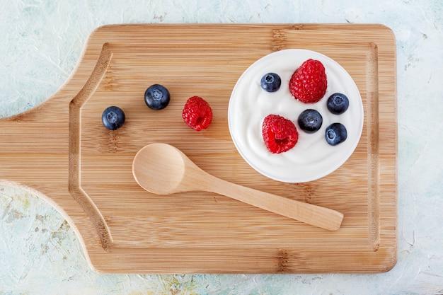 Yogurt con lampone e mirtilli su una tavola di legno