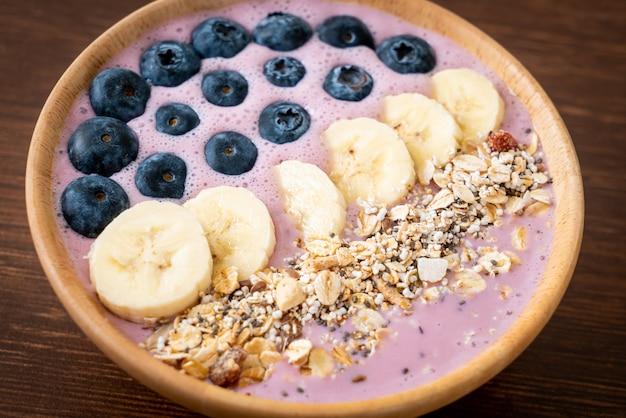 Ciotola di frullato di yogurt o yogurt con bacche blu, banana e muesli - stile di cibo sano