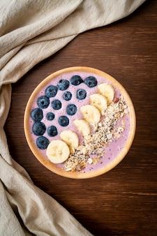 Ciotola per frullato di yogurt o yogurt con bacche blu, banana e muesli. stile alimentare sano