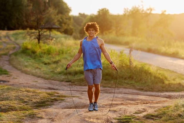 Corda di salto dell'uomo bello di misura di yong in parco un giorno soleggiato.