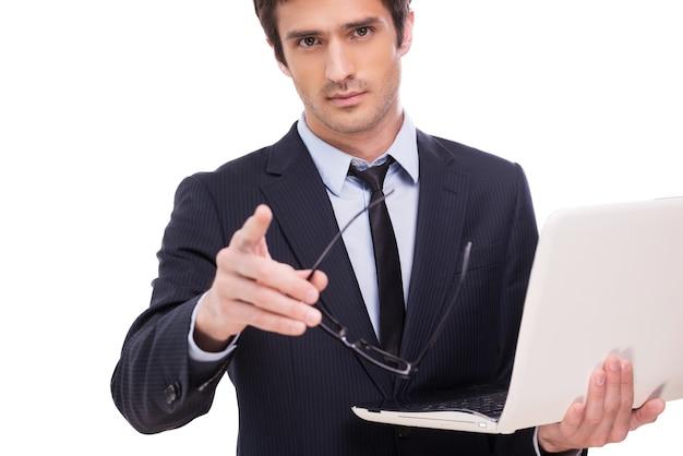 Puoi assolutamente fidarti di me! bel giovane in abiti da cerimonia che tiene in mano un laptop e ti indica