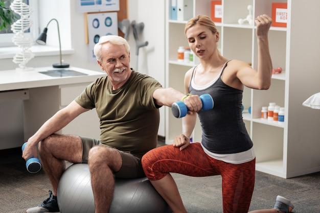 Puoi farlo. uomo invecchiato positivo che solleva un manubrio mentre è seduto sulla palla fitness