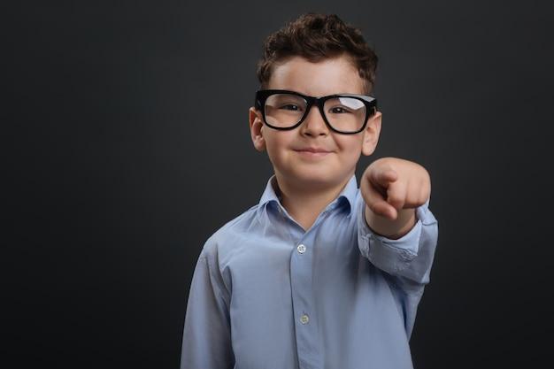 Puoi farlo. dolce bel ragazzo fiducioso che ti incoraggia a fare qualcosa mentre indossi gli occhiali e in piedi isolato su sfondo grigio