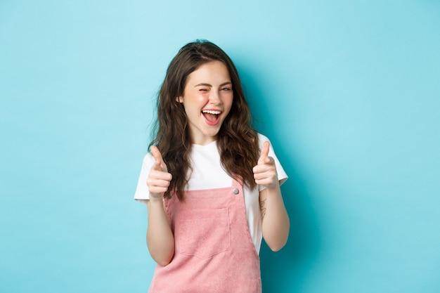 Puoi farlo. bella ragazza bruna allegra strizzando l'occhio e sorridente, puntando il dito verso la telecamera, lodando il buon lavoro, invitando all'evento, in piedi su sfondo blu