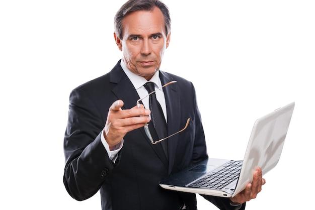Puoi fidarti di me! fiducioso uomo maturo in abiti da cerimonia che tiene in mano un laptop e ti indica mentre sta in piedi isolato su sfondo bianco