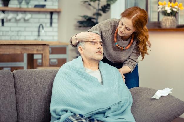 Ti senti male. piacevole donna dai capelli rossi in piedi dietro il marito mentre si preoccupa per lui