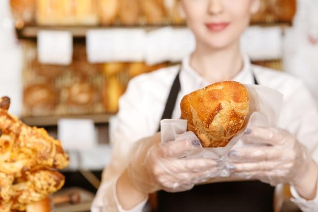 Lo adorerai! messa a fuoco selettiva su un lavoratore di panetteria pane fresco che tiene fuori