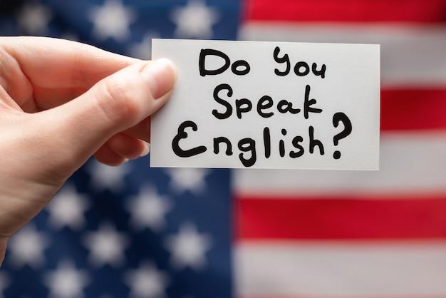 Parli testo inglese su una carta. sfondo bandiera americana.