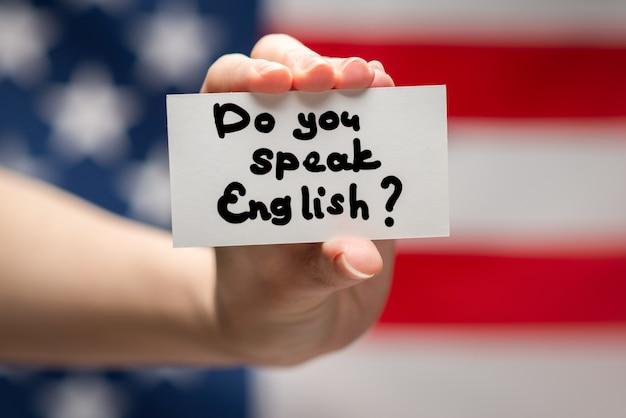 Parli testo inglese su una carta. superficie della bandiera americana.