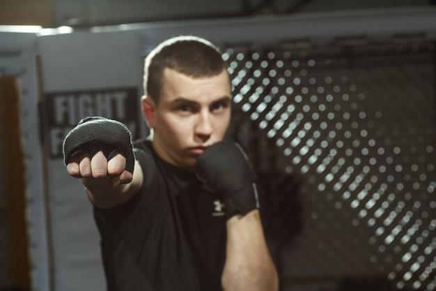 Non lo vuoi! colpo di un combattente maschio professionista in posa in gabbia da combattimento ottagono