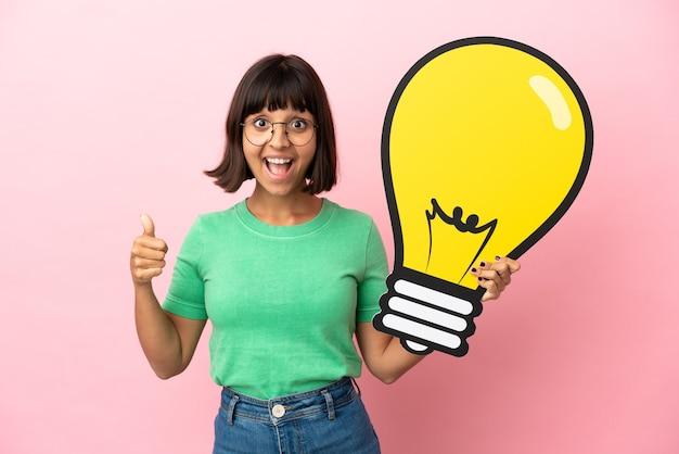 Giovane donna che tiene in mano un'icona a forma di lampadina e pensa