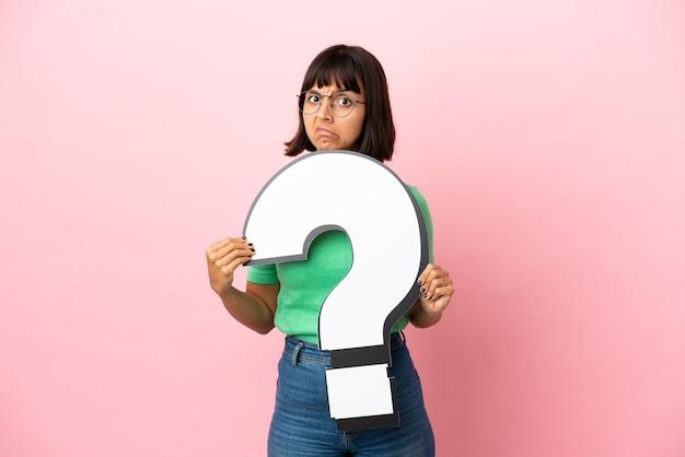 Giovane donna che tiene in mano un'icona con un punto interrogativo e con un'espressione triste