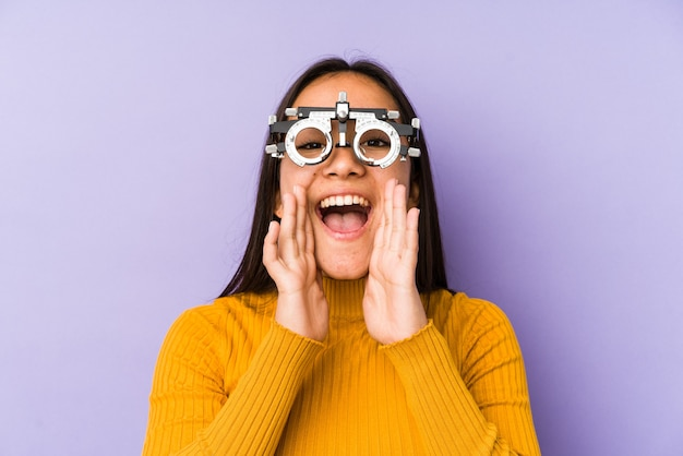 Donna indiana di youn con gli occhiali di optometria che grida eccitati alla parte anteriore.
